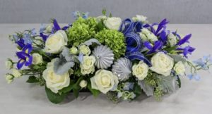 Starlight Holiday centerpiece to adorn a holiday table of winter roses, blue iris, hydrangea, dusty miller with accents of silver and shimmering blue bow.